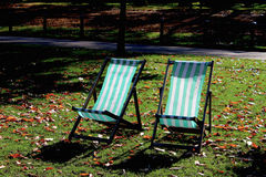 Two Deck Chairs. Two empty green and white striped deckchairs sit in the Autumn sun in a park Stock Images