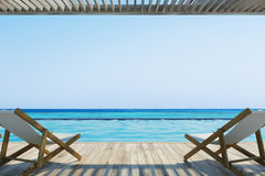 Two deck chairs near a pool Stock Photos
