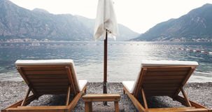 Two deck-chairs with sun umbrella on a sea beach surrounded by mountains – Summer  Resort Romantic Vacation. Two deck-chairs with sun umbrella on a sea beach stock video