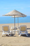 Two deck chairs and umbrella on sandy beach Stock Photos