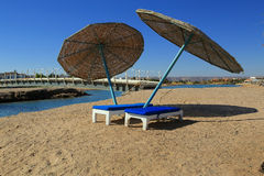 Two deck chairs with umbrellas. Stock Photo