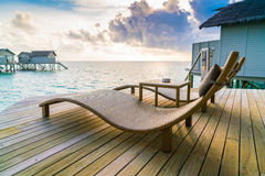 Two deck chairs on the wooden floor in water villa sunset time , Stock Image