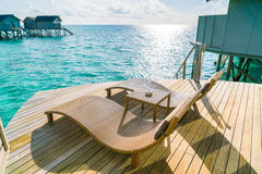 Two deck chairs on the wooden floor in water villa sunset time , Stock Photography