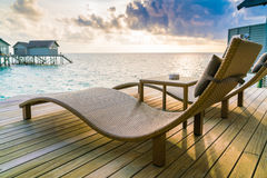 Two deck chairs on the wooden floor in water villa sunset time , Stock Photo