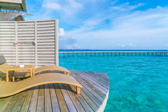 Two deck chairs on the wooden floor in water villa sunset time , Royalty Free Stock Photography