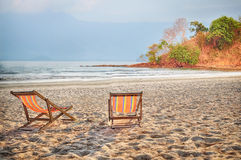Two deckchair canvas on sand at the tropical beach background Royalty Free Stock Image