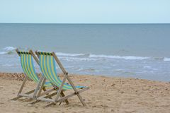 Two deckchairs on the beach Stock Image