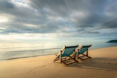 Two deckchairs on the beach at sunset with a tropical sea background. Travel and Vacation in Summer at sea stock photo