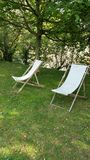 Two canvas deckchairs on lawn. Two canvas deck chairs on lawn in garden in shade of trees in French country garden Royalty Free Stock Photo
