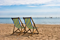 Two deckchairs on a sandy beach Royalty Free Stock Images