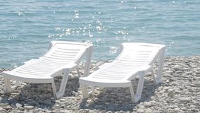 Two deckchairs stand on a pebble beach. Two deckchairs stand on a pebble beach stock video footage
