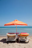 Two deckchairs under parasol on beach Stock Images
