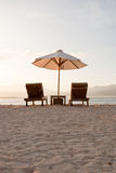 Two deckchairs on a white sandy beach Stock Image