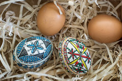 Two decorated easter eggs. And two fresh organic eggs on straw Stock Images