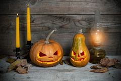 Two decorated pumpkins for a Halloween on a mystical autumn background. With candles and gas lamp royalty free stock image