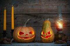 Two decorated pumpkins for a Halloween on a mystical autumn background. With candles and gas lamp royalty free stock photo
