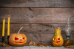 Two decorated pumpkins for a Halloween on a mystical autumn background with candles. And gas lamp royalty free stock images