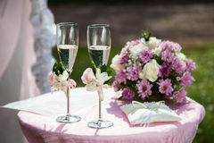 Two decorated wineglasses with champagne, ring pillows and wedding flowers are on the table for wedding ceremony. royalty free stock photo