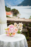 Two decorated wineglasses with champagne and wedding bouquet fro. M peonies and roses are on the table for wedding ceremony at gorgeous view which includes stock image