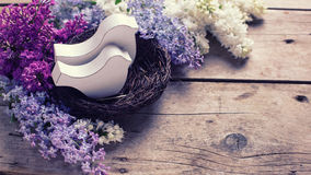 Two decorative birds in nest and  fresh aromatic lilac flowers Stock Image