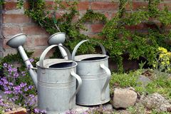 Watering cans in the garden Royalty Free Stock Photos