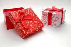 Two decorative gift boxes with hearts printed isolated open red Stock Photos