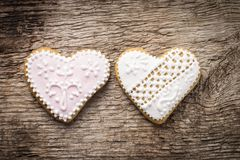 Two decorative heart cookies on wood background Stock Photos
