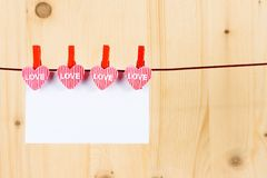 Two decorative hearts with greeting card hanging on wood background, concept of valentine day in love Royalty Free Stock Images