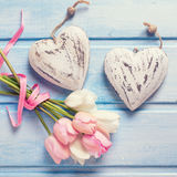 Two decorative hearts and tender white and pink spring tulips  o. N  blue wooden background. Pastel colors. Shubby chic. Selective focus. Square, toned image Royalty Free Stock Photography