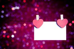 Two decorative red hearts with greeting card hanging on blue and violet light bokeh background, concept of valentine day royalty free stock photography