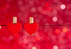 Two decorative red hearts hanging against red light bokeh background, concept of valentine day. Two decorative red hearts hanging against red light bokeh Royalty Free Stock Photo
