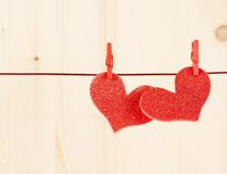 Two decorative red hearts hanging on wood background, concept of valentine day Stock Image