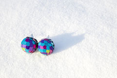 Two decorative spheres on a white snow. Stock Photos