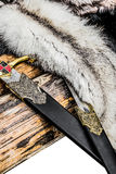 Two decorative swords and furs across a log Royalty Free Stock Image