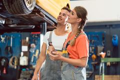 Two dedicated auto mechanics smiling while checking the wheels of a car Stock Image