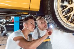 Two dedicated auto mechanics tuning a car through the modification of the rims royalty free stock photo