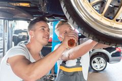 Two dedicated auto mechanics tuning a car stock photo