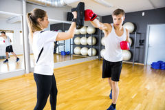 Two dedicated people training boxing at the fitness gym Stock Photos