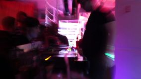 Two deejays playing music in the nightclub. Active camera zoom moves stock video