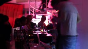 Two deejays playing music in the nightclub stock video footage