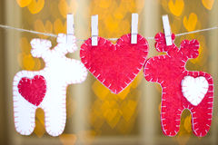 Two deer made of felt and heart on clothespins. Royalty Free Stock Image