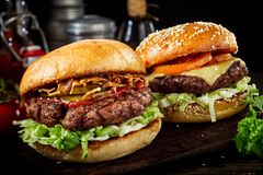 Two delicious beef burgers with salad trimmings. One a cheeseburger and the other with ham and ketchup on a dark wooden board in a close up view Royalty Free Stock Photo