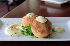 Two delicious crab cakes with lemon caper remoulade served over a bed of arugula Royalty Free Stock Photo
