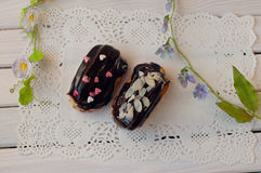Two delicious dark chocolate eclairs lay on white lace serviette Royalty Free Stock Photos
