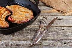 Two delicious grilled piece of pork on a cutting board with a knife for meat. And rosemary on wooden rustic background top view close up stock photos