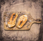 Two delicious grilled salmon steak with spices on a cutting board wooden rustic background top view close up Stock Photos