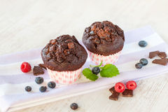 Two delicious homemade chocolate muffins in colored cooking pape Royalty Free Stock Photography