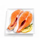 Two delicious raw salmon slice on white plate. Two delicious raw salmon slice with spices on white plate, top view Stock Photography