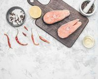 Two delicious raw salmon steak with lemon, seasoning and pepper on white background, place for text stock photo