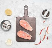 Two delicious raw salmon steaks with lemon, seasoning pepper on a white background, top view royalty free stock image